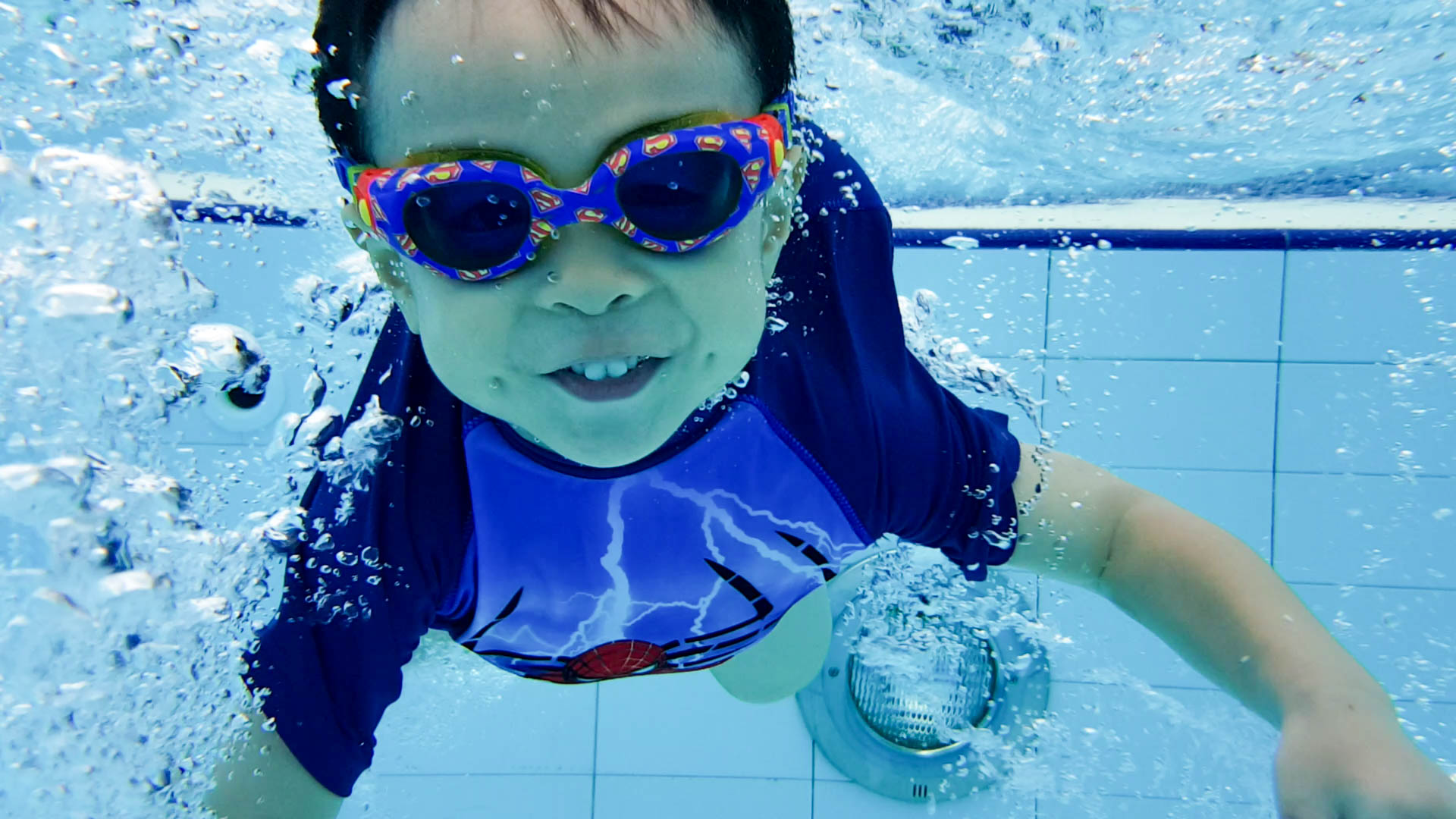 Toddler blowing bubbles during swimming lessons