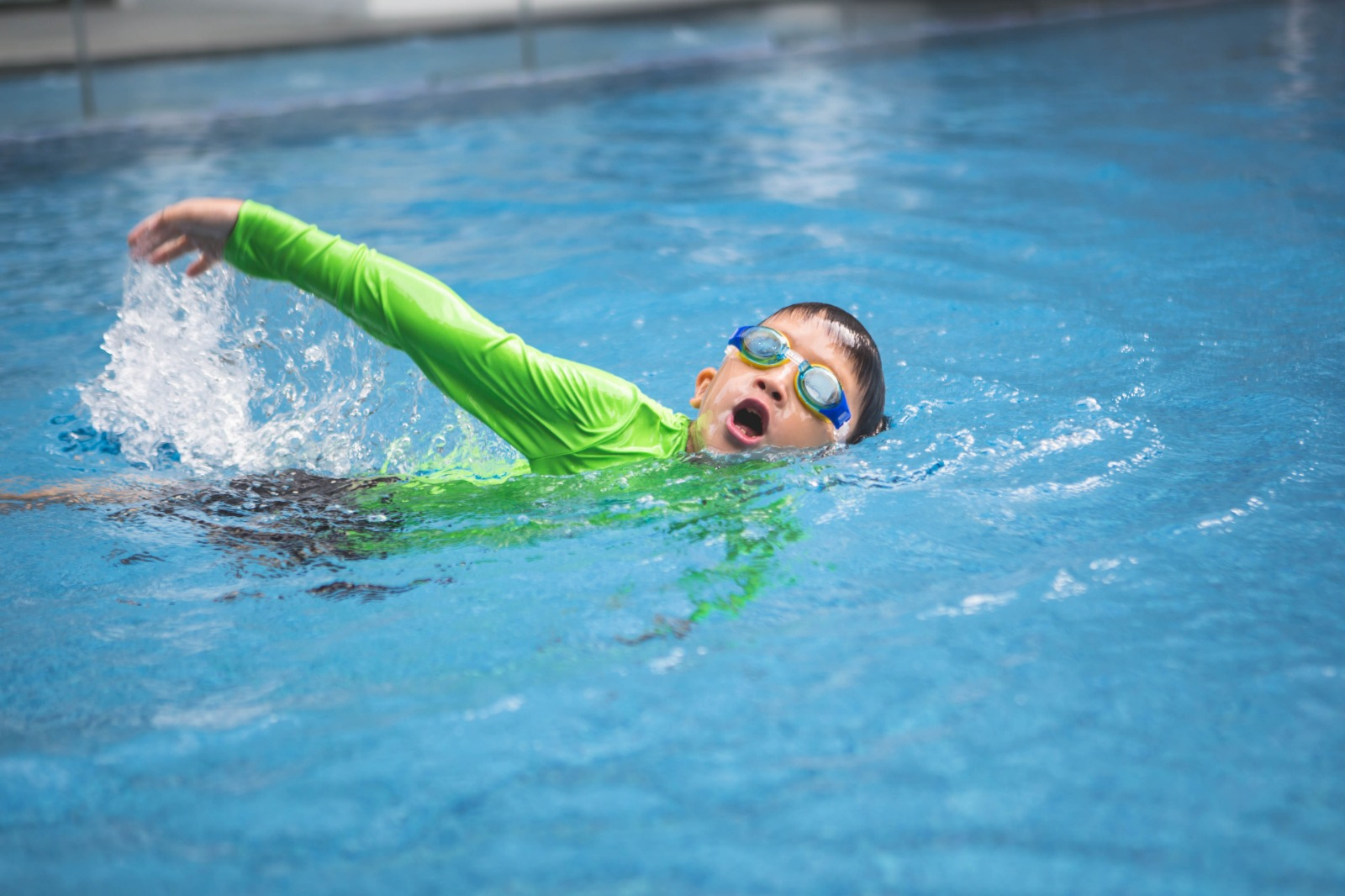 Young boy swimming in private lessons